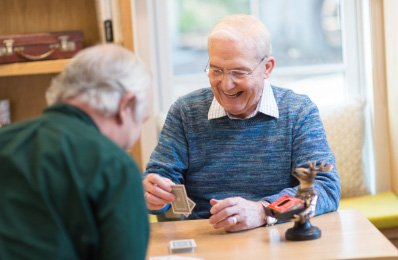 Two Residents play cards in care home
