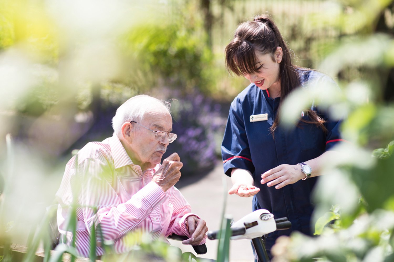 Elderly resident and nurse gardening in care home