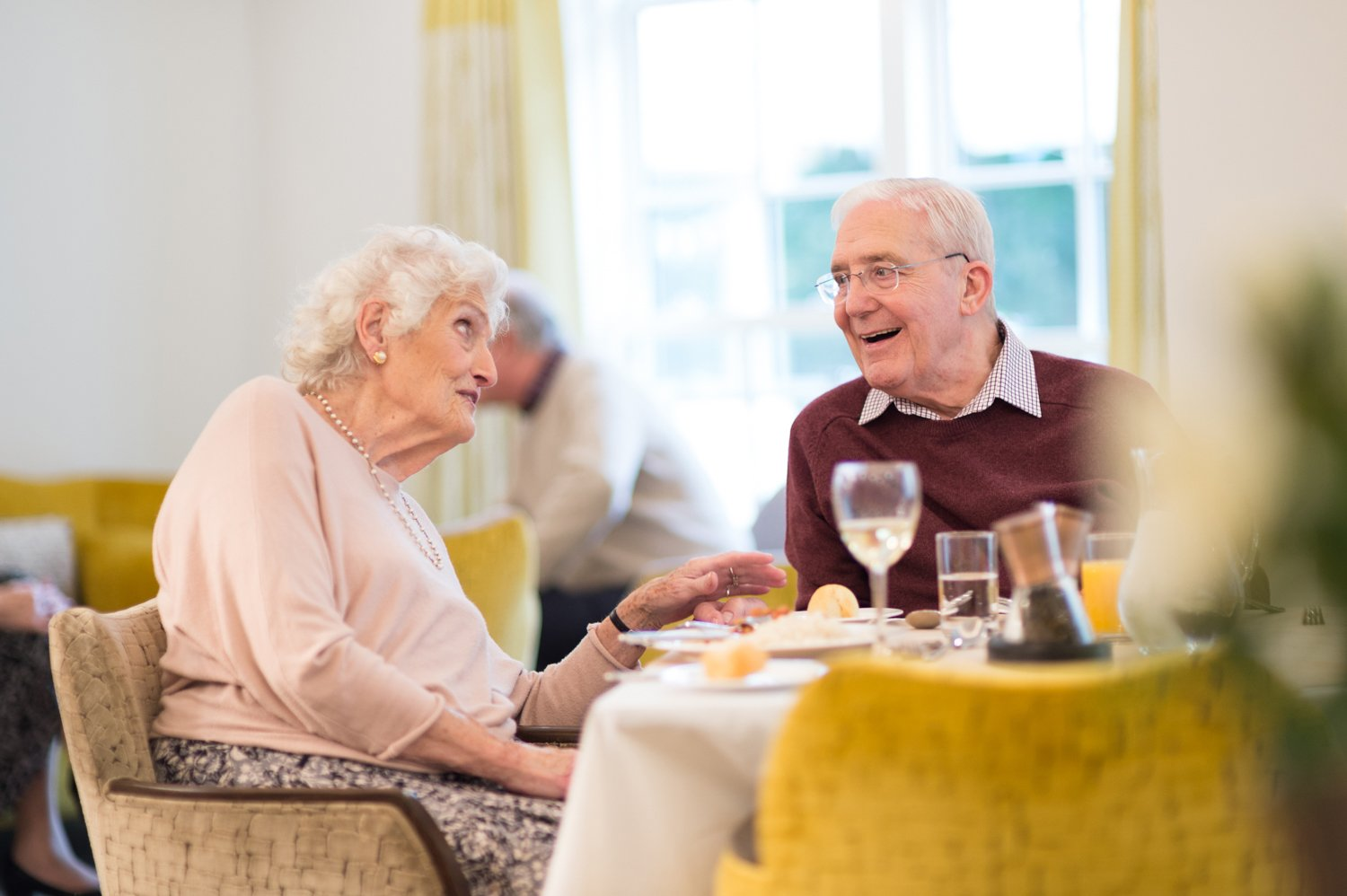 two elderly residents dine in care home